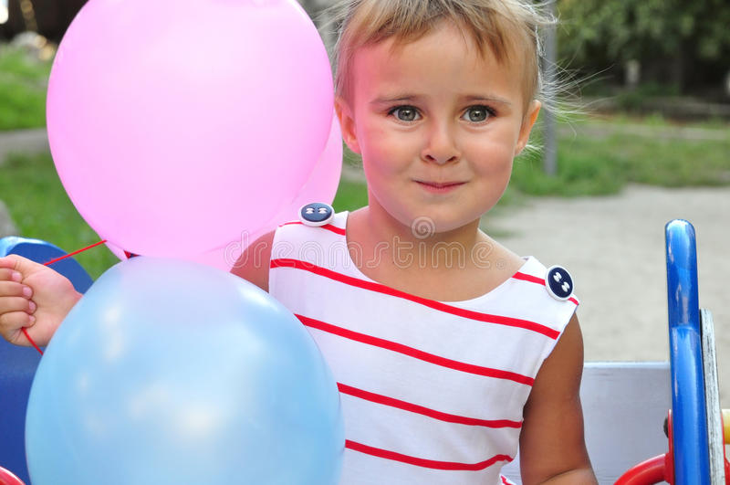 Adorable little girl playing with balloons. Close-up portarit of adorable little girl smiling and playing with colurful balloons royalty free stock images