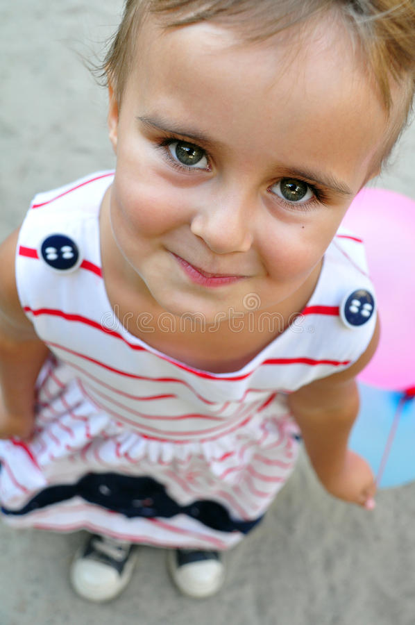 Adorable little girl playing with balloons looking up. Close-up portarit of adorable little girl smiling and playing with colurful balloons looks up royalty free stock image