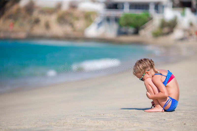 Adorable little girl playing at beach during european vacation stock photos