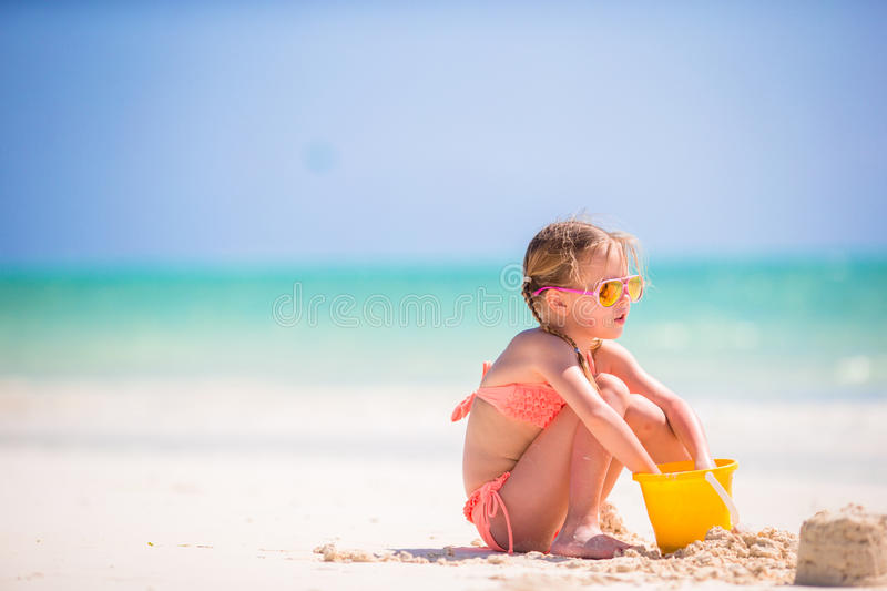 Adorable little girl playing with beach toys on the white beach stock image