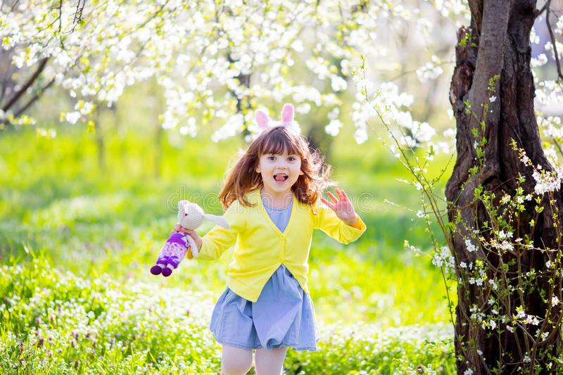 Adorable little girl playing in blooming apple tree garden on Easter egg hunt. Child in spring fruit orchard with cherry blossom stock photos