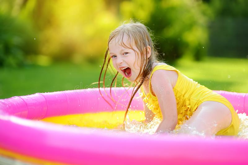 Adorable little girl playing in inflatable baby pool. Happy kid splashing in colorful garden play center on hot summer day. Summer activities for kids royalty free stock photography