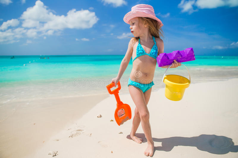 Adorable little girl playing with sand on a royalty free stock photography