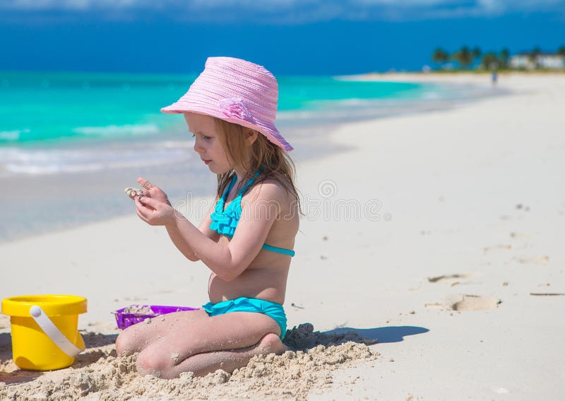 Adorable little girl playing with sand on a stock images