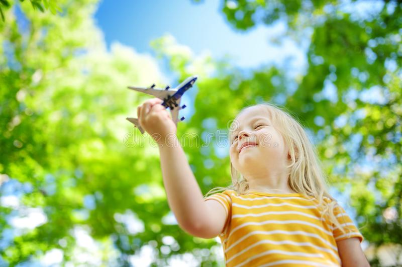 Adorable little girl playing with small toy airplane outdoors. On warm and sunny summer day royalty free stock images