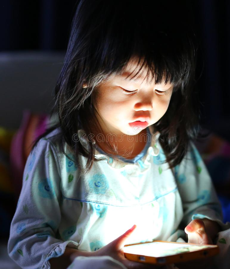 Adorable little girl playing smartphone lying on a bed stock images