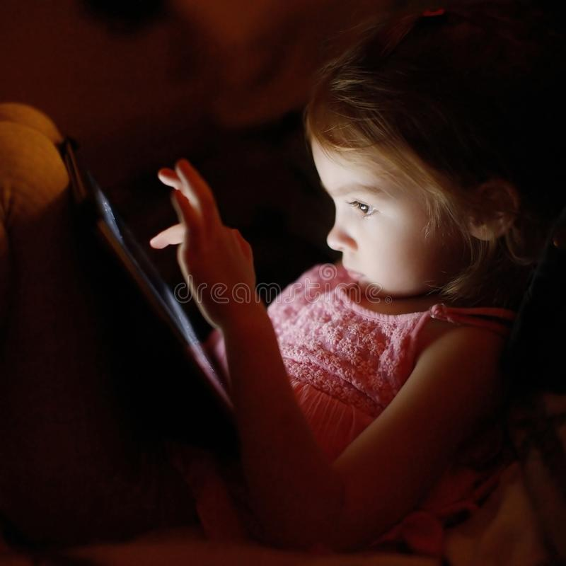 Adorable little girl playing on a tablet stock photos