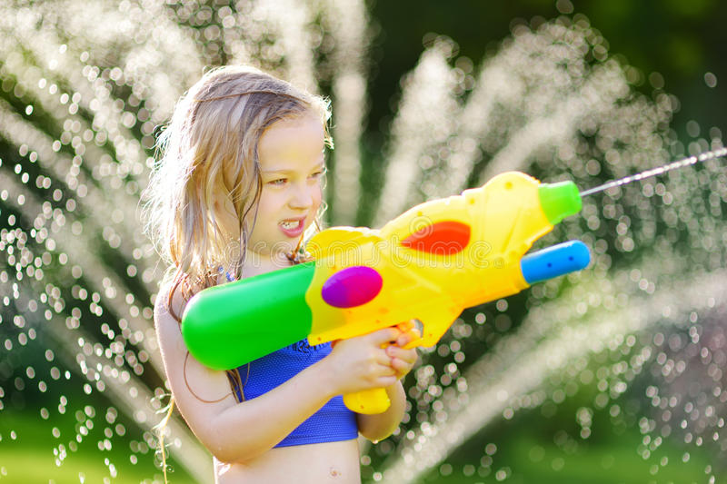 adorable little girl playing with water gun on hot summer day cute child having fun with water. Black Bedroom Furniture Sets. Home Design Ideas