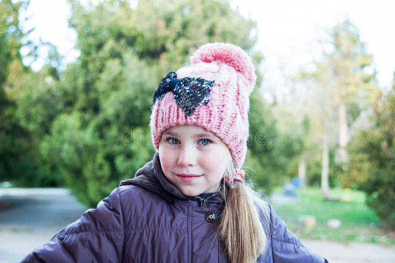 Adorable little girl posing. Wearing winter coat and hat. stock photo