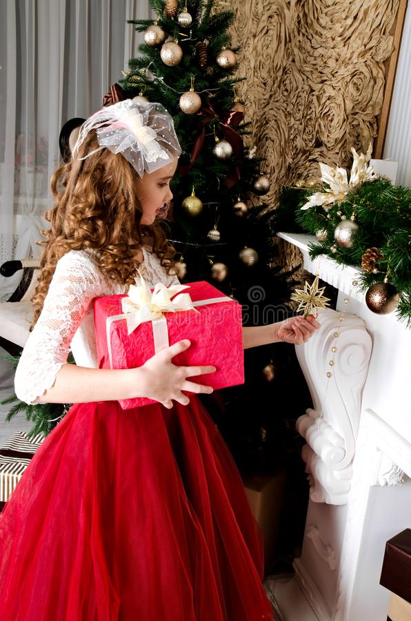 Adorable little girl in princess dress with gift box near fir tr royalty free stock photography