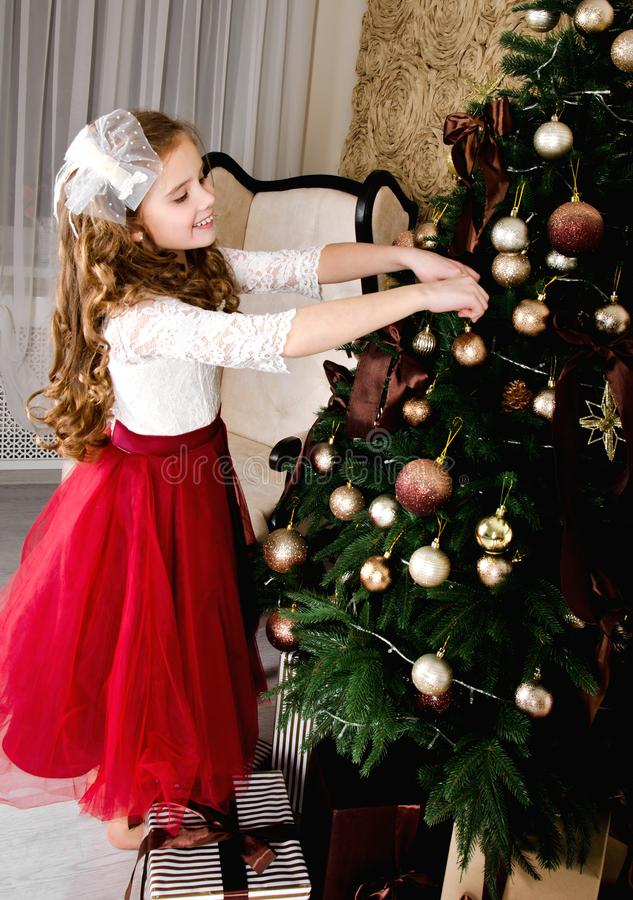 Adorable little girl in princess dress hanging up the balls on. Adorable happy smiling little girl in princess dress hanging up the balls on fir tree in stock photography