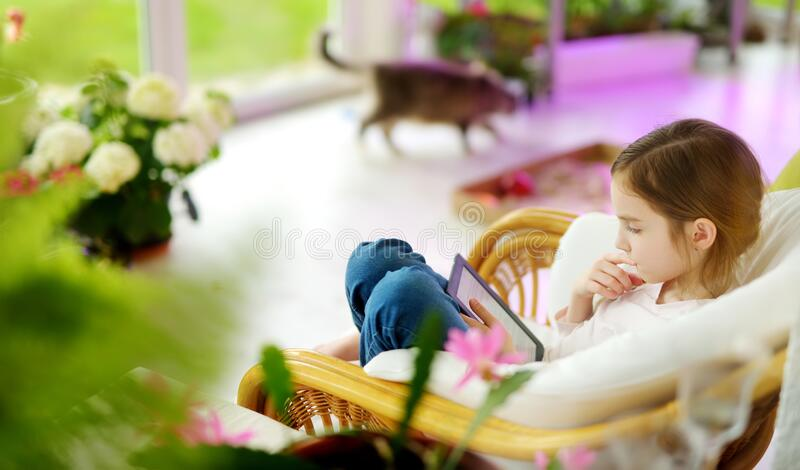 Adorable little girl reading an ebook in white living room on beautiful summer day. Smart schoolgirl doing her homework at home royalty free stock photos