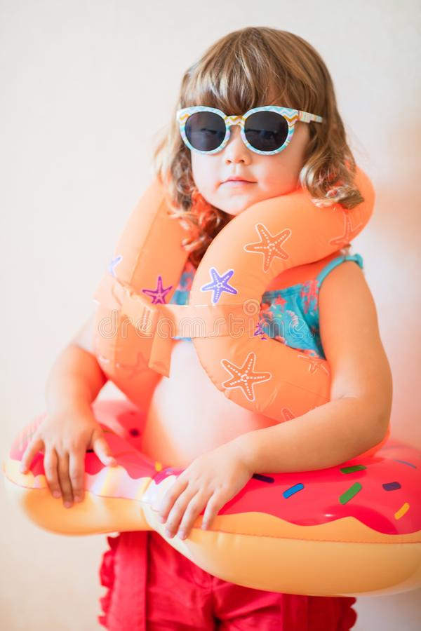 Adorable little girl ready to go for the beach, wearing sunglasses, inflatable over-sleeves floats and inflatable donut float ring. Safety in the water concept stock image
