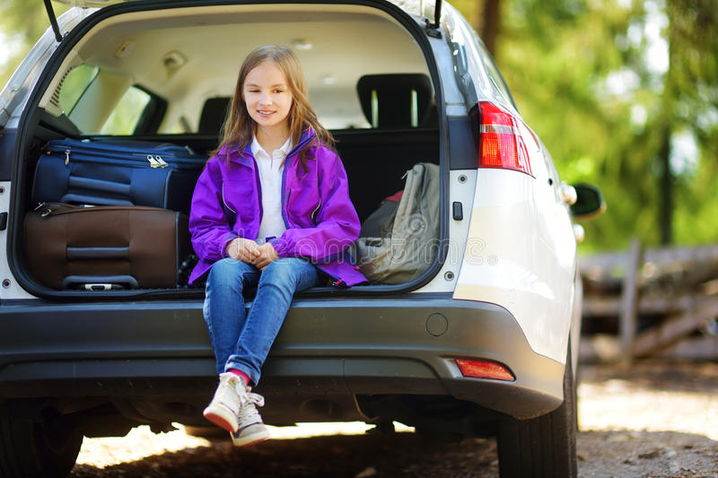Adorable little girl ready to go on vacations with her parents. Kid relaxing in a car before a road trip. Traveling by car with kids royalty free stock images