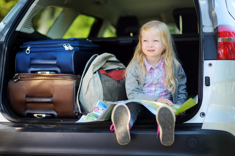 Adorable little girl ready to go on vacations with her parents. Kid sitting in a car examining a map. Traveling by car with kids stock photography