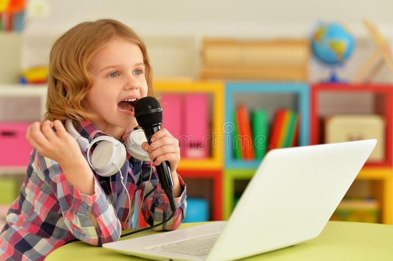 Portrait of adorable little girl singing karaoke with modern laptop stock photos