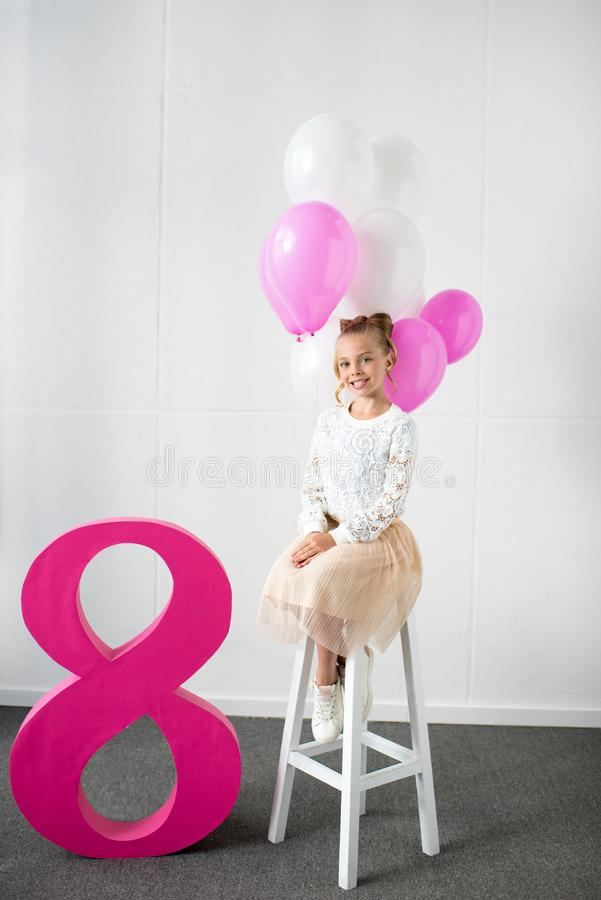 adorable little girl sitting on stool with balloons and smiling at camera stock image