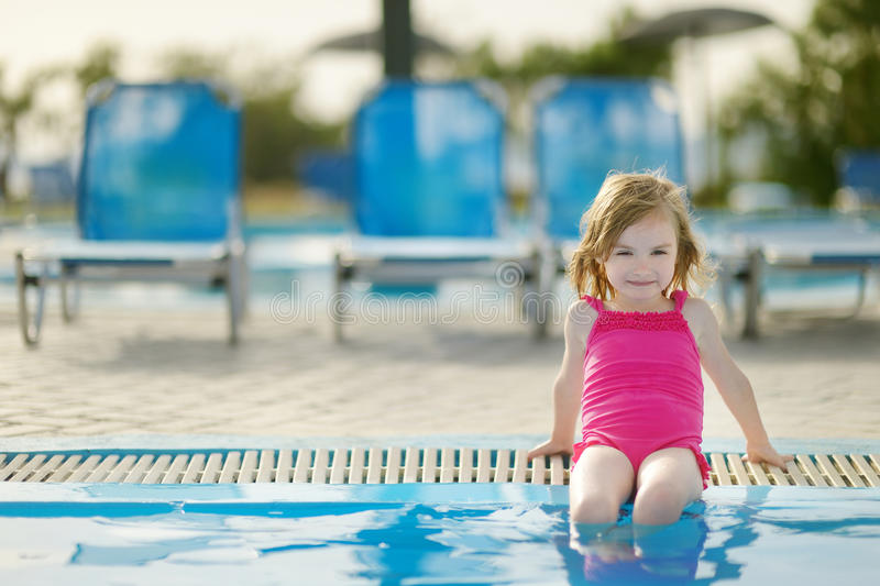 Adorable little girl sitting by a swimming pool royalty free stock images