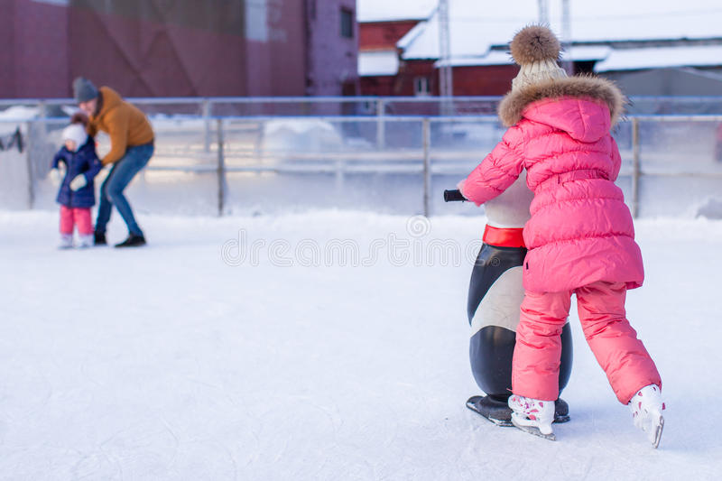 Adorable little girl skating on the ice-rink. This image has attached release royalty free stock image
