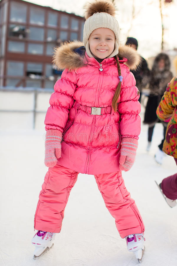 Adorable little girl skating on the ice-rink. This image has attached release stock photography