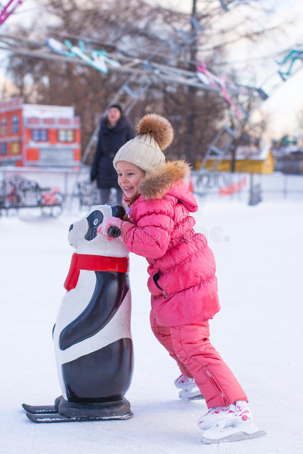 Adorable little girl skating on the ice-rink. This image has attached release stock photo