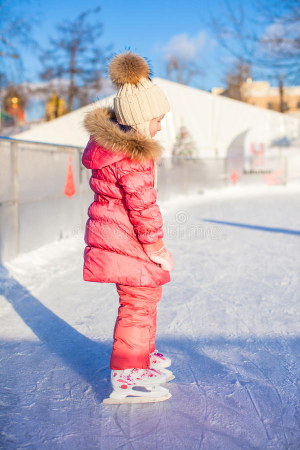 Adorable little girl skating on the ice-rink. This image has attached release royalty free stock images