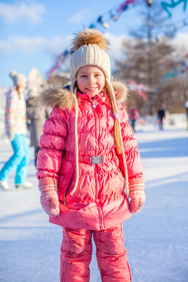 Adorable little girl skating on the ice-rink. This image has attached release stock image