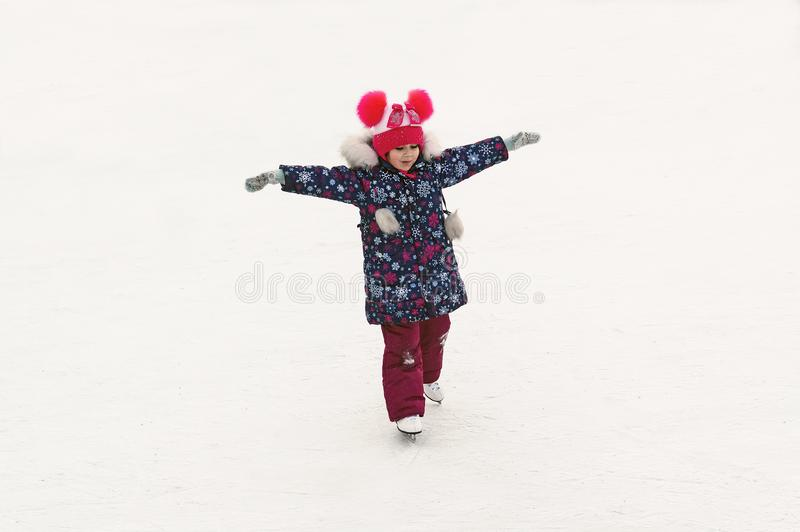 Adorable little girl skating on the ice rink outdoors. Winter outdoor activities. Amateur sport royalty free stock photo