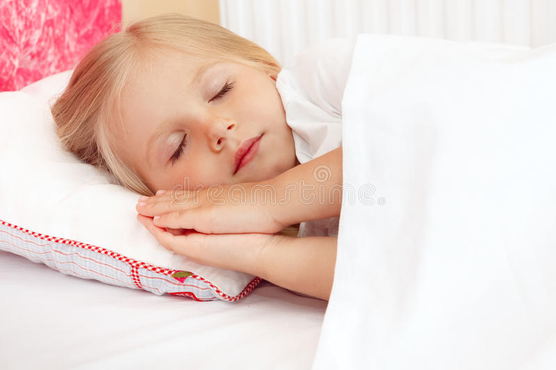 Adorable little girl sleeping in the bed stock images