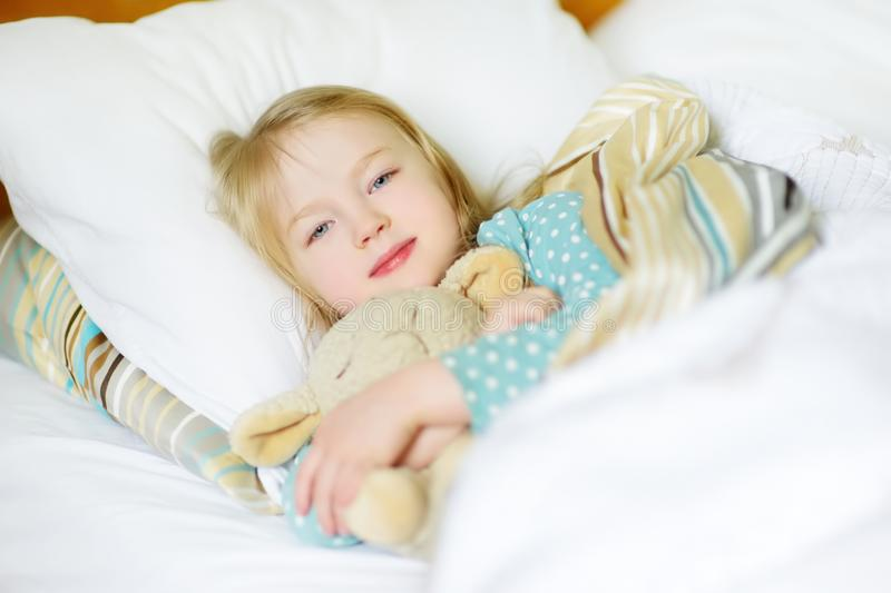 Adorable little girl sleeping in the bed with her toy. Tired child taking a nap under white blanket. stock photo