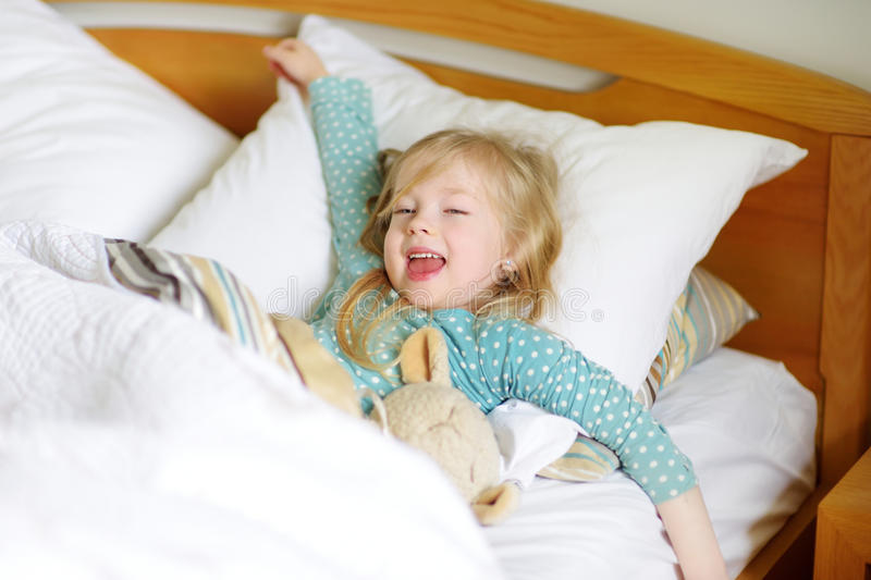 Adorable little girl sleeping in the bed with her toy stock photos