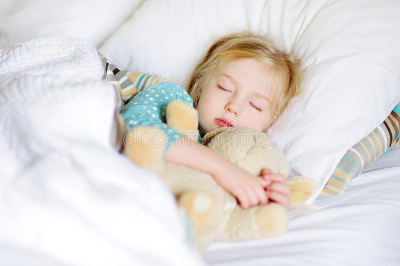 Adorable little girl sleeping in the bed with her toy royalty free stock images