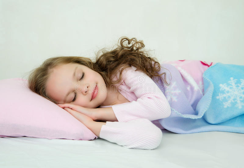 Adorable little girl sleeping in her bed stock images
