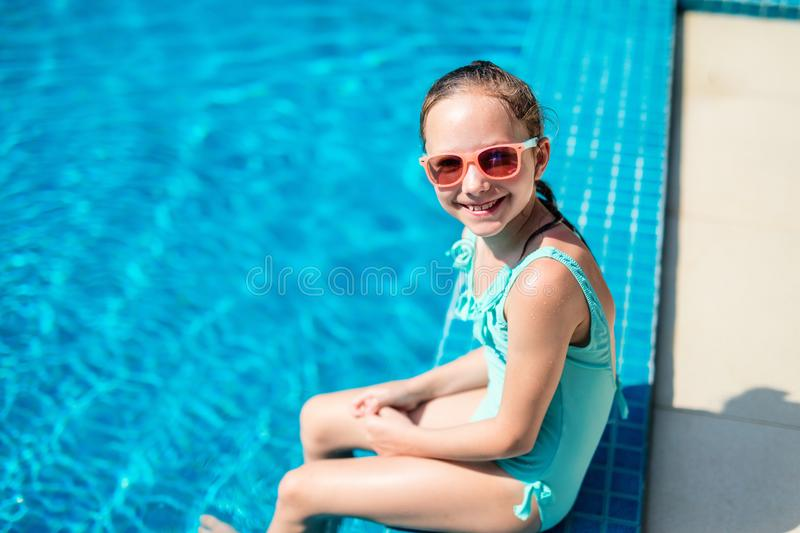 Little girl in swimming pool. Adorable little girl at swimming pool having fun during summer vacation stock photography