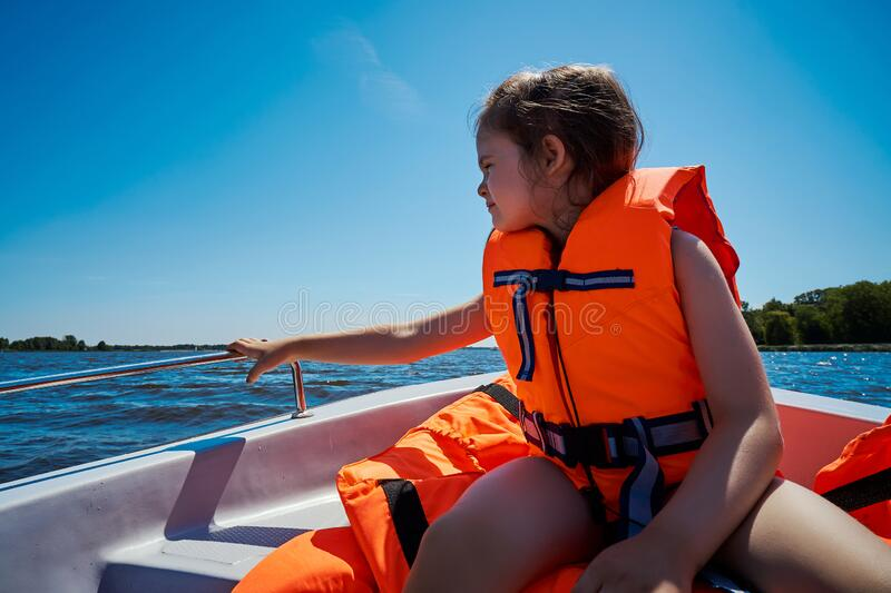 Little girl in a swimming vest sits in a motorboat royalty free stock photos