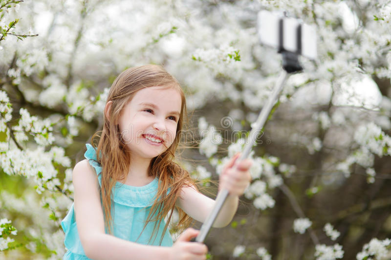 Adorable little girl taking a photo of herself with a selfie stick. On beautiful summer day royalty free stock photo