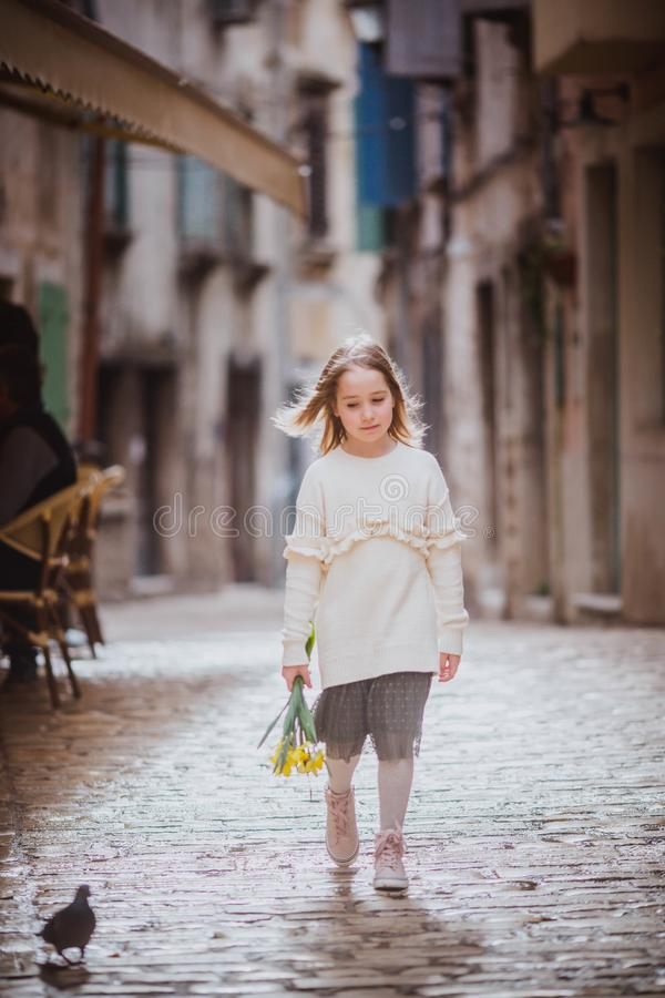 Adorable little girl in trend clothes standing in old town in sunny spring day with yellow flowers royalty free stock photo