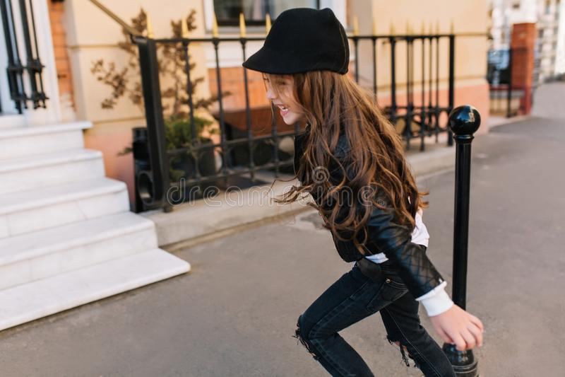 Adorable little girl in trendy black jeans and hat running on the street spending time at fresh air in school vacation royalty free stock photo