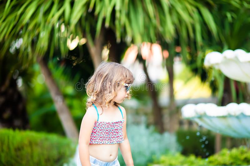 Adorable little girl at the tropical resort, standing by the palm three at the sunny summer day stock images