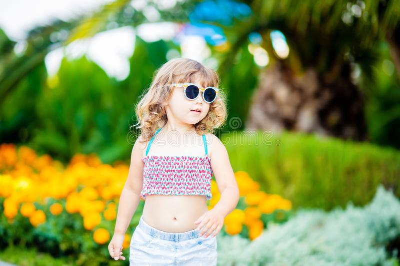 Adorable little girl at the tropical resort, standing by the palm three at the sunny summer day stock photography