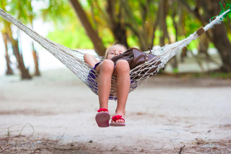 Adorable little girl on tropical vacation relaxing. Adorable little girl on summer vacation relaxing in hammock royalty free stock photo
