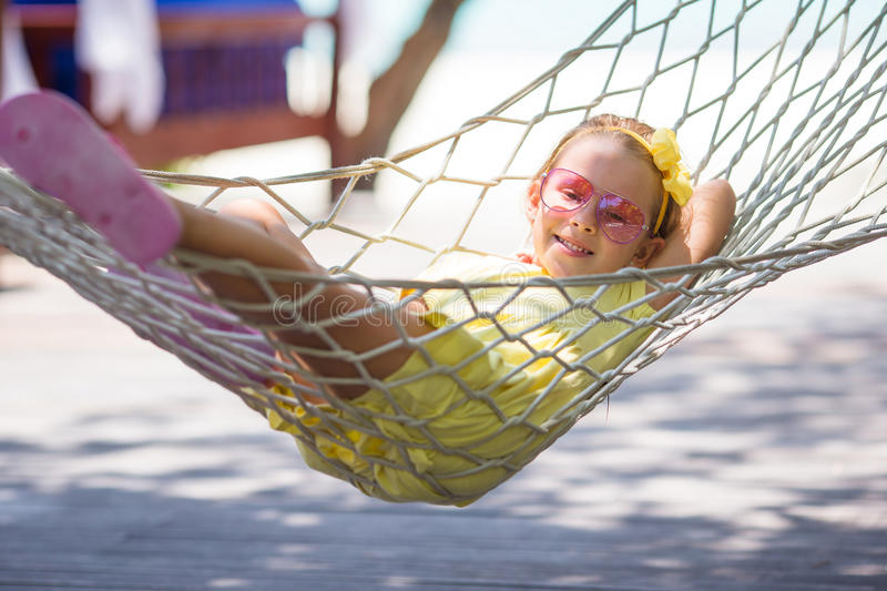 Adorable little girl on tropical vacation relaxing. Adorable little girl on summer vacation relaxing in hammock stock photo