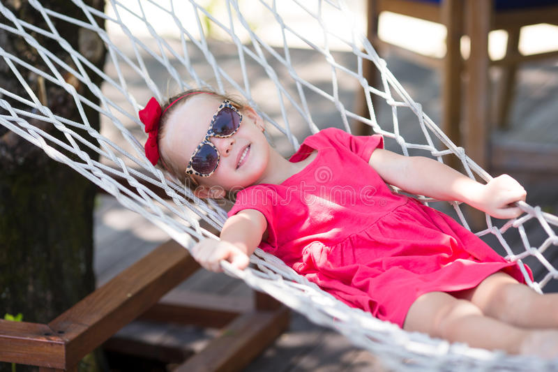 Adorable little girl on tropical vacation relaxing. Adorable little girl on summer vacation relaxing in hammock stock photography