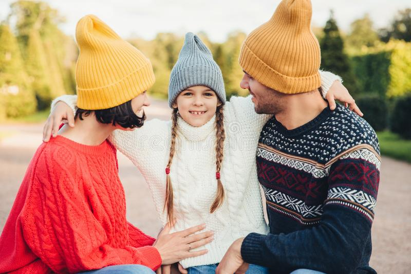 Adorable little girl with two pigtails, wears warm knitted hat and sweater, embrace her affectionate parents, admire beautiful nat royalty free stock photography