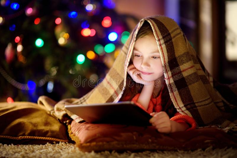 Adorable little girl using a tablet pc by a fireplace on Christmas evening royalty free stock images