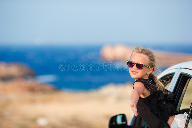 Adorable little girl on vacation travel by car background beautiful landscape. Family on vacation. Summer holiday and car travel concept stock image