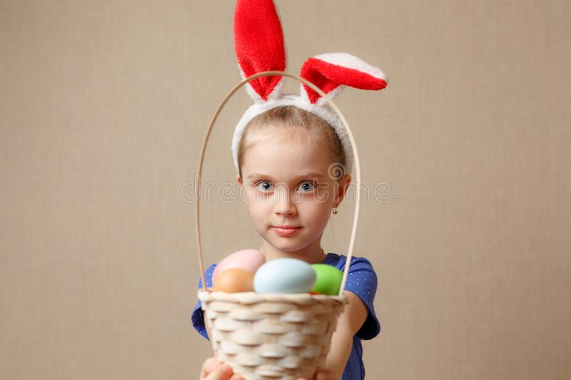 Adorable little girl wearing bunny ears playing with Easter eggs stock photography