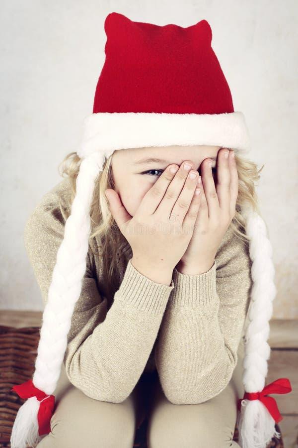 Funny little girl hiding eyes. Adorable little girl wearing christmas studio portrait of happy preschool girl royalty free stock photography