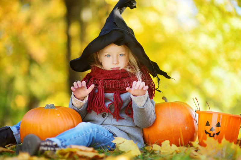 Adorable little girl wearing halloween costume having fun on a pumpkin patch on autumn day stock photo