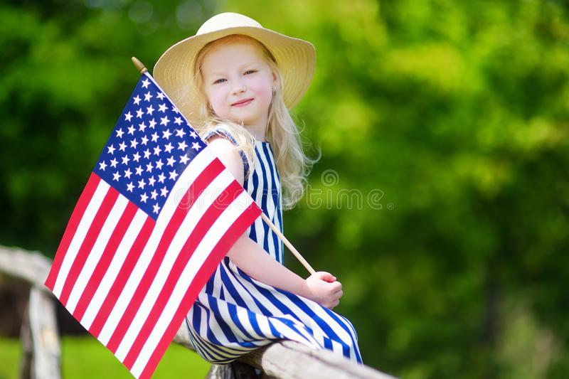 Adorable little girl wearing hat holding american flag outdoors on beautiful summer day. Independence Day concept stock image